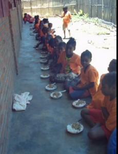 Enfant prenant leur repas à midi sur le trottoir de l'école d'alphabétisation.